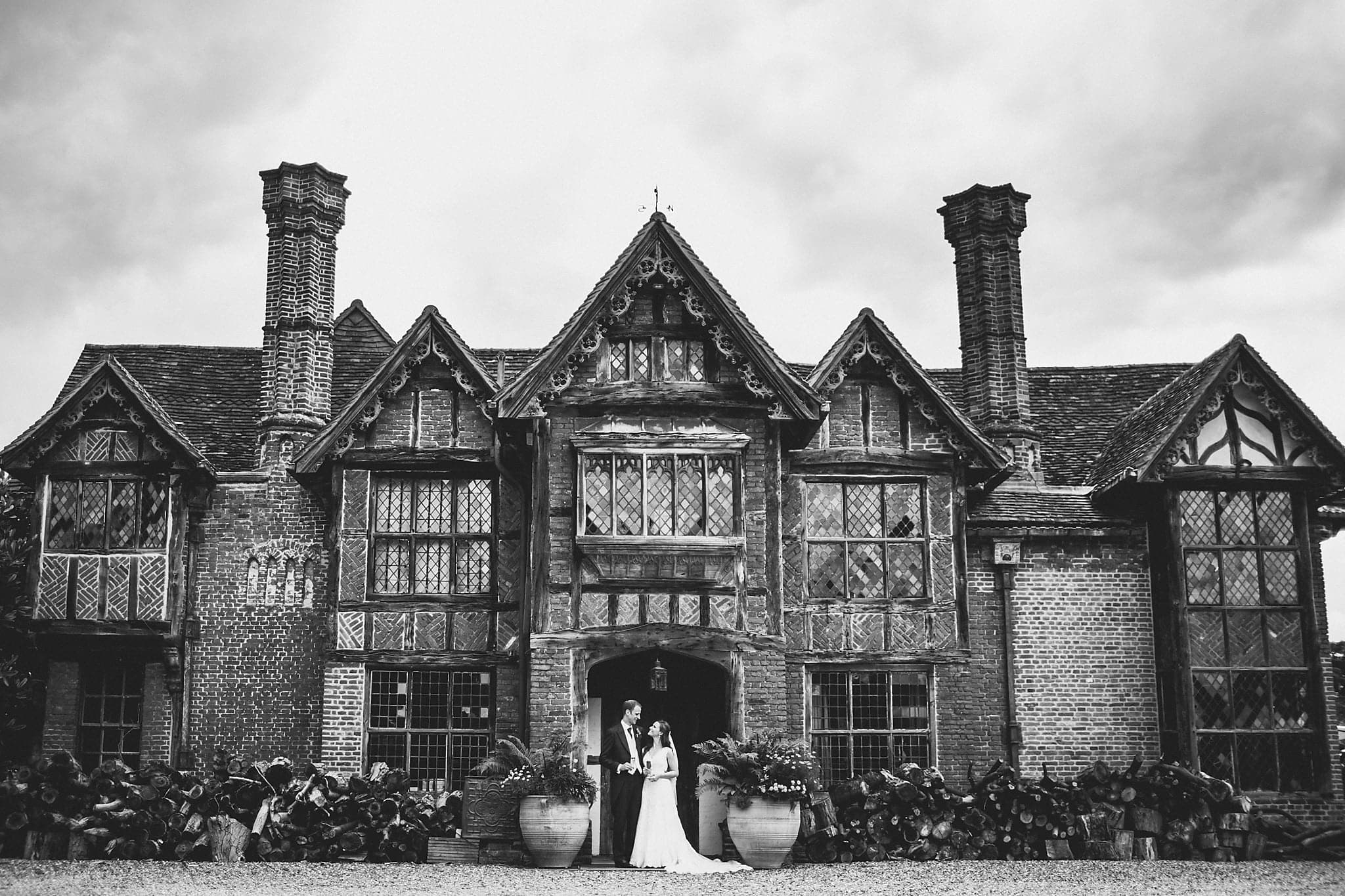 Black and white shot of bride and groom in front of Tudor Manor at Dorney Court
