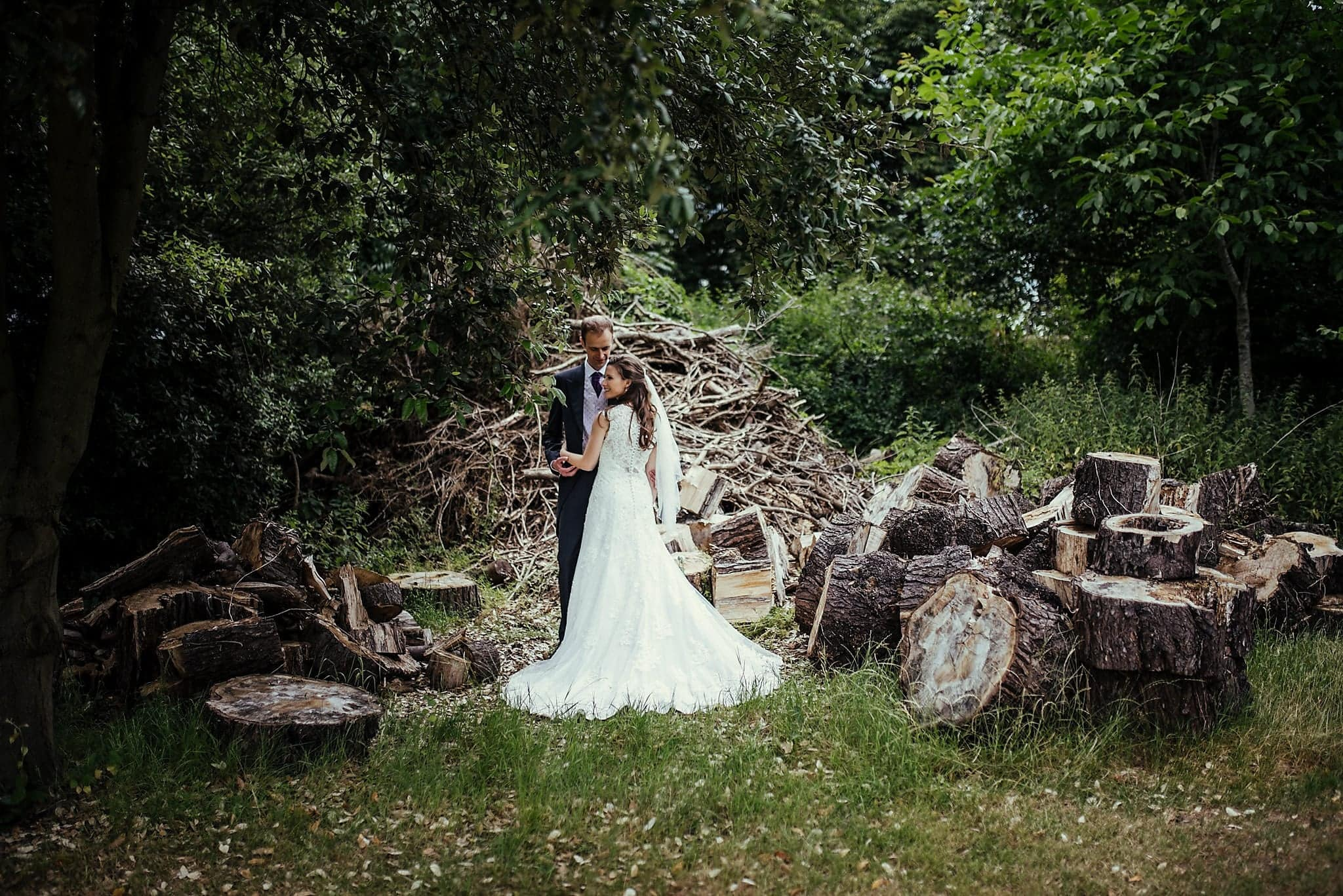 Bride and groom pose amid woodpile in the grounds of Dorney Court