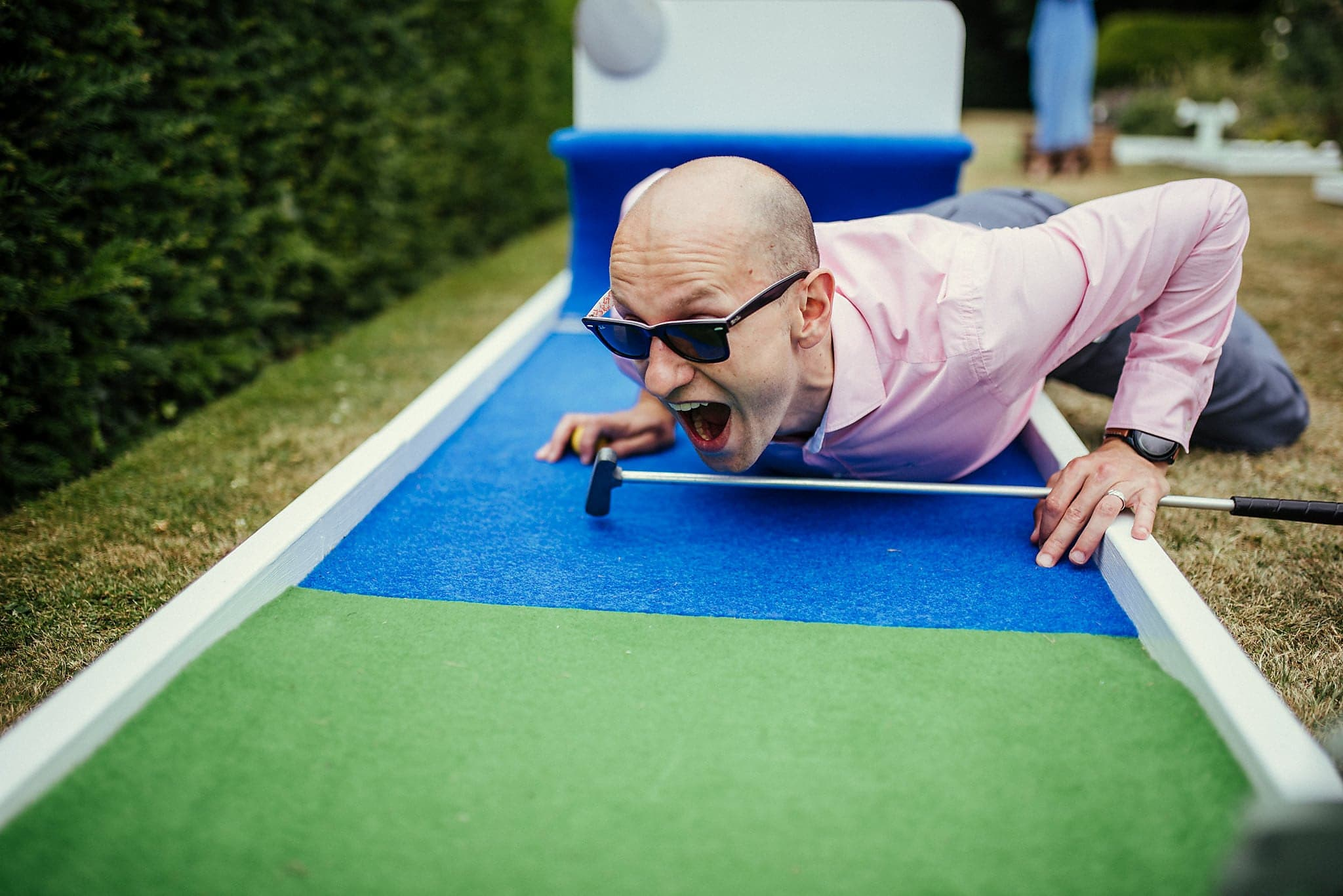 Male wedding guest gets competitive during mini golf tournament at Dorney Court tipi wedding