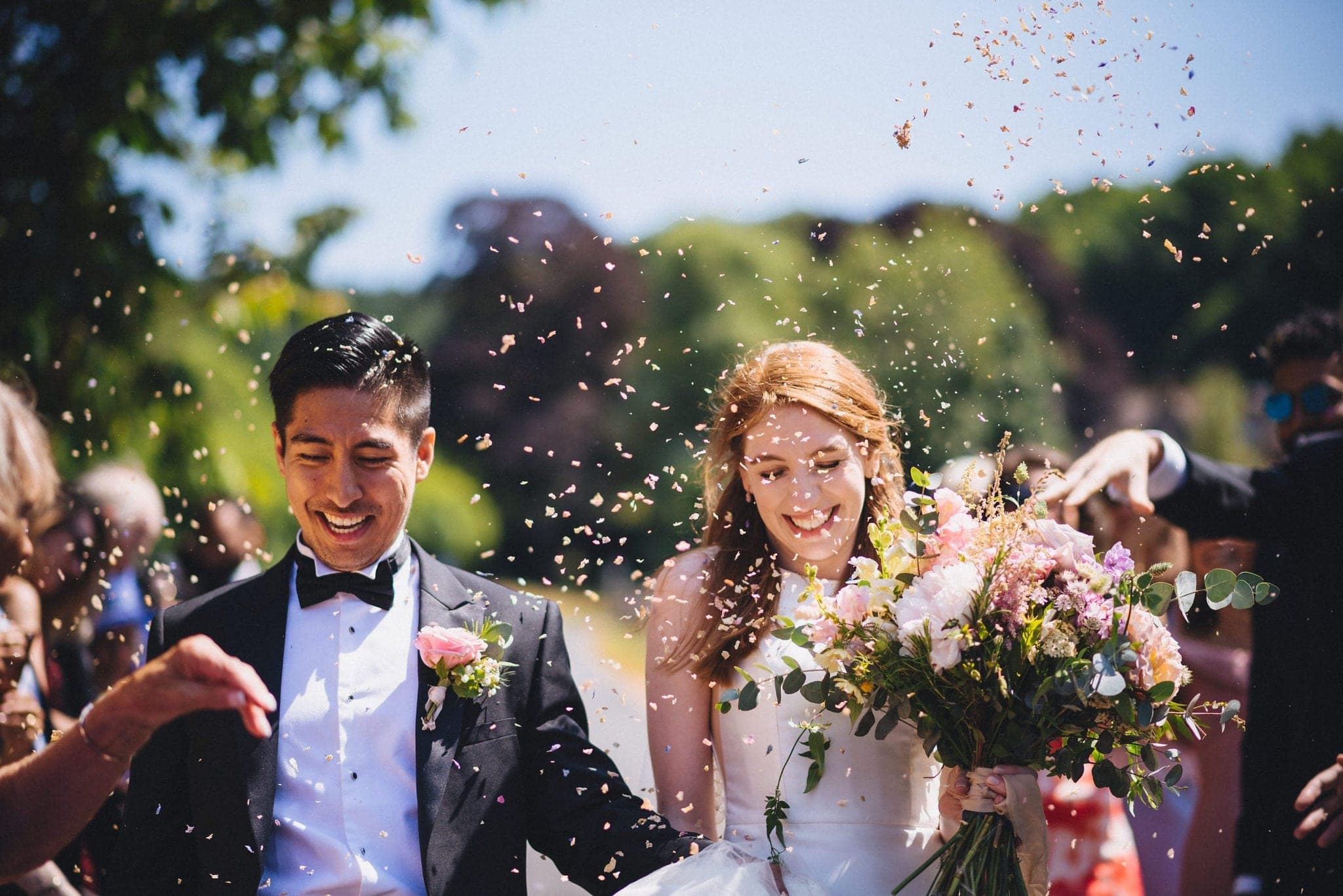 Bride and Groom walking through their confetti shower