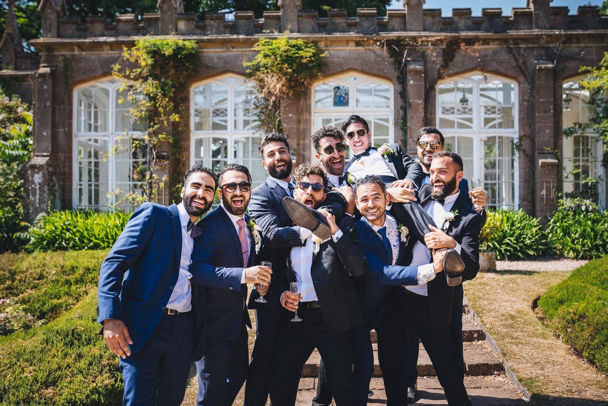 Groomsmen carrying the groom on their shoulders and laughing at a glamorous St Audries Park Wedding