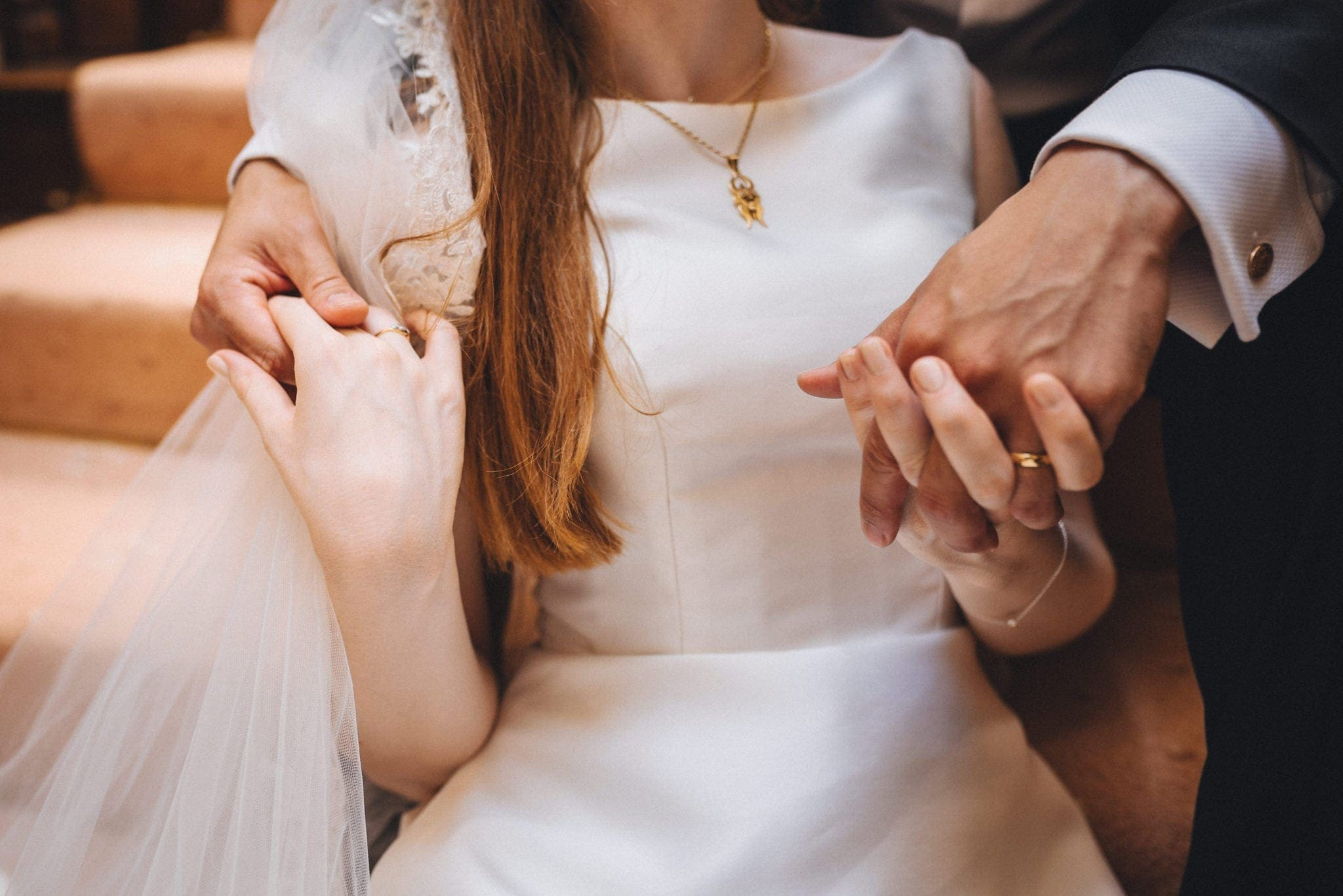 Closeup of the bride and groom holding hands