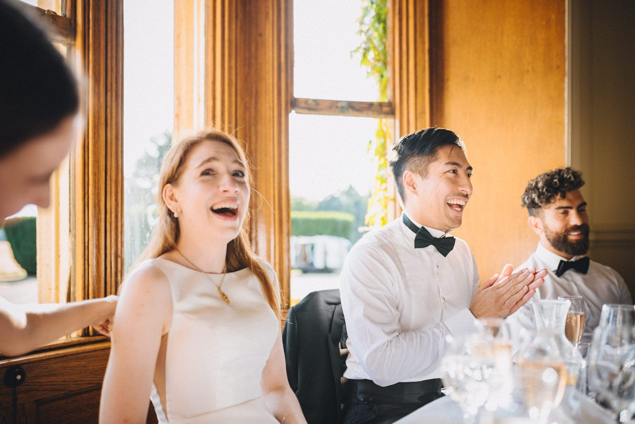 Bride and groom laughing at wedding speeches