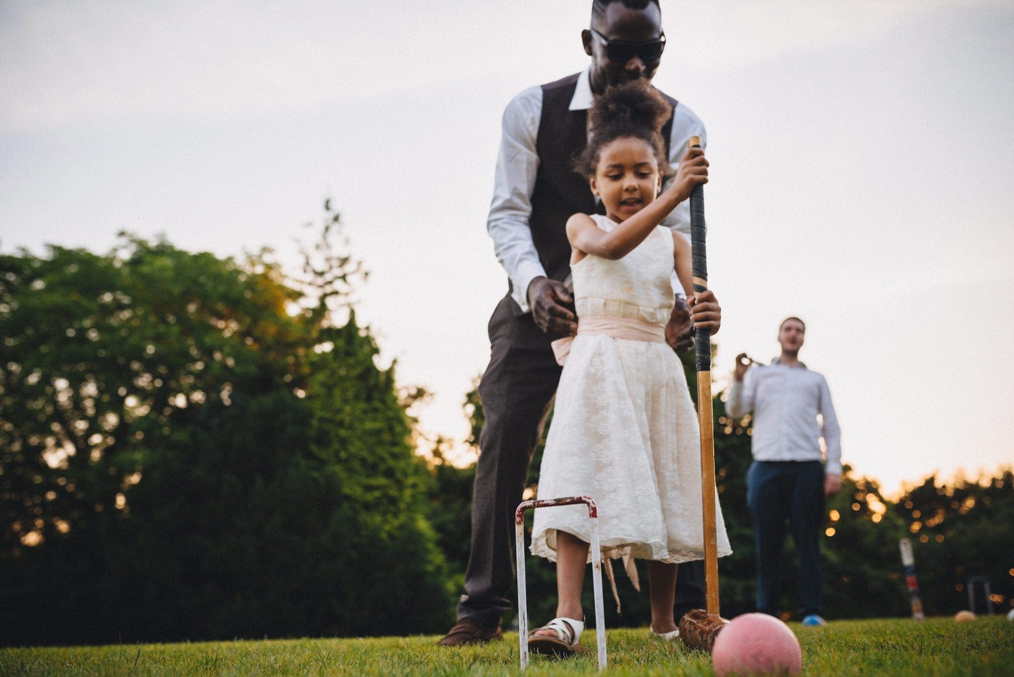 Wedding guest helping his daughter play croquet at St Audries Park