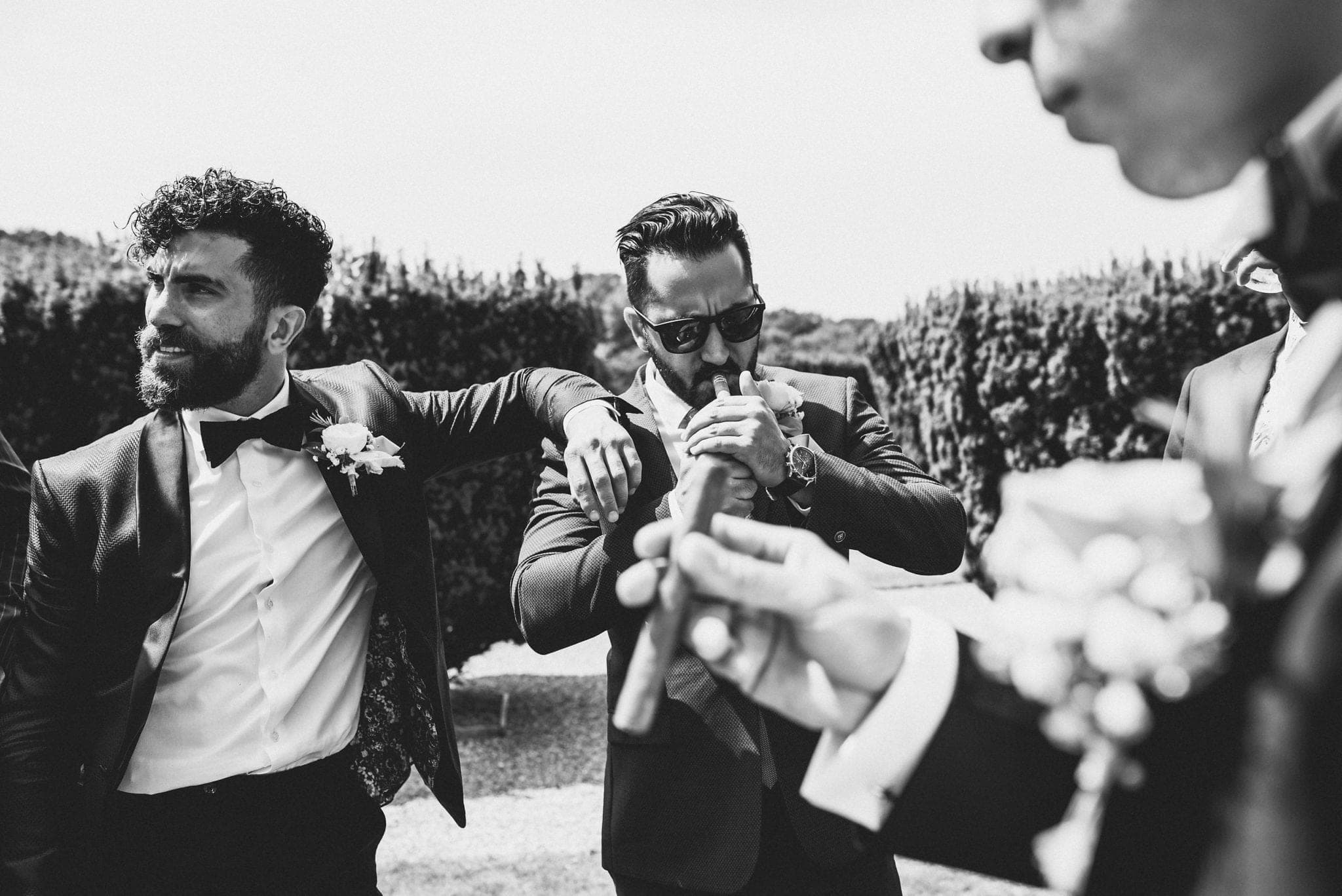 Groom and groomsmen smoking cigars in the rose garden at St Audries Park
