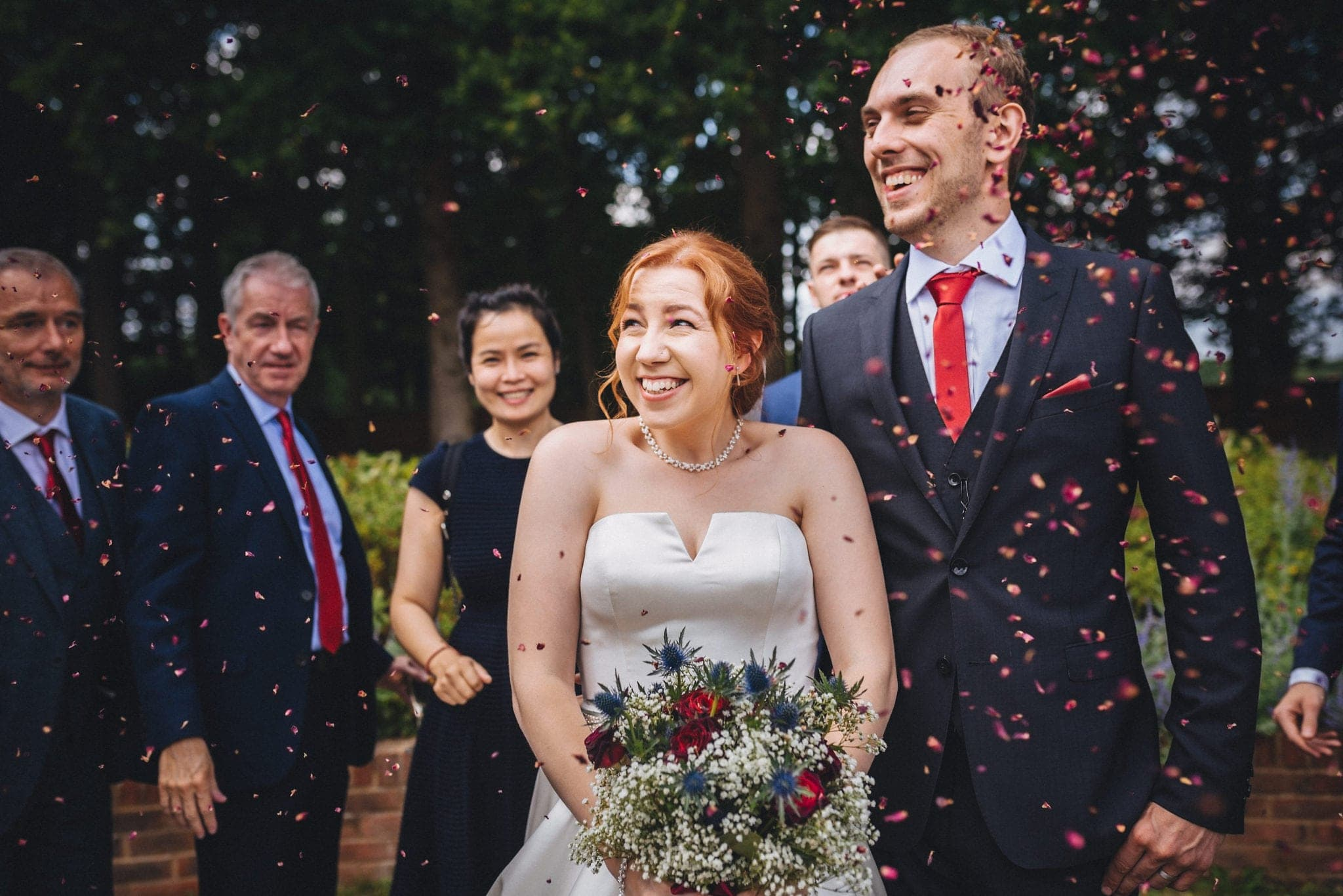 Bride and groom showered in red petal confetti at their Intimate Hever Hotel Wedding