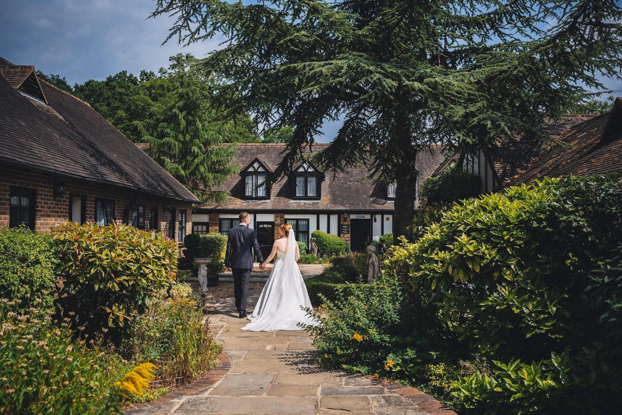 Bride and groom walking at their Joyful Intimate Hever Hotel Wedding