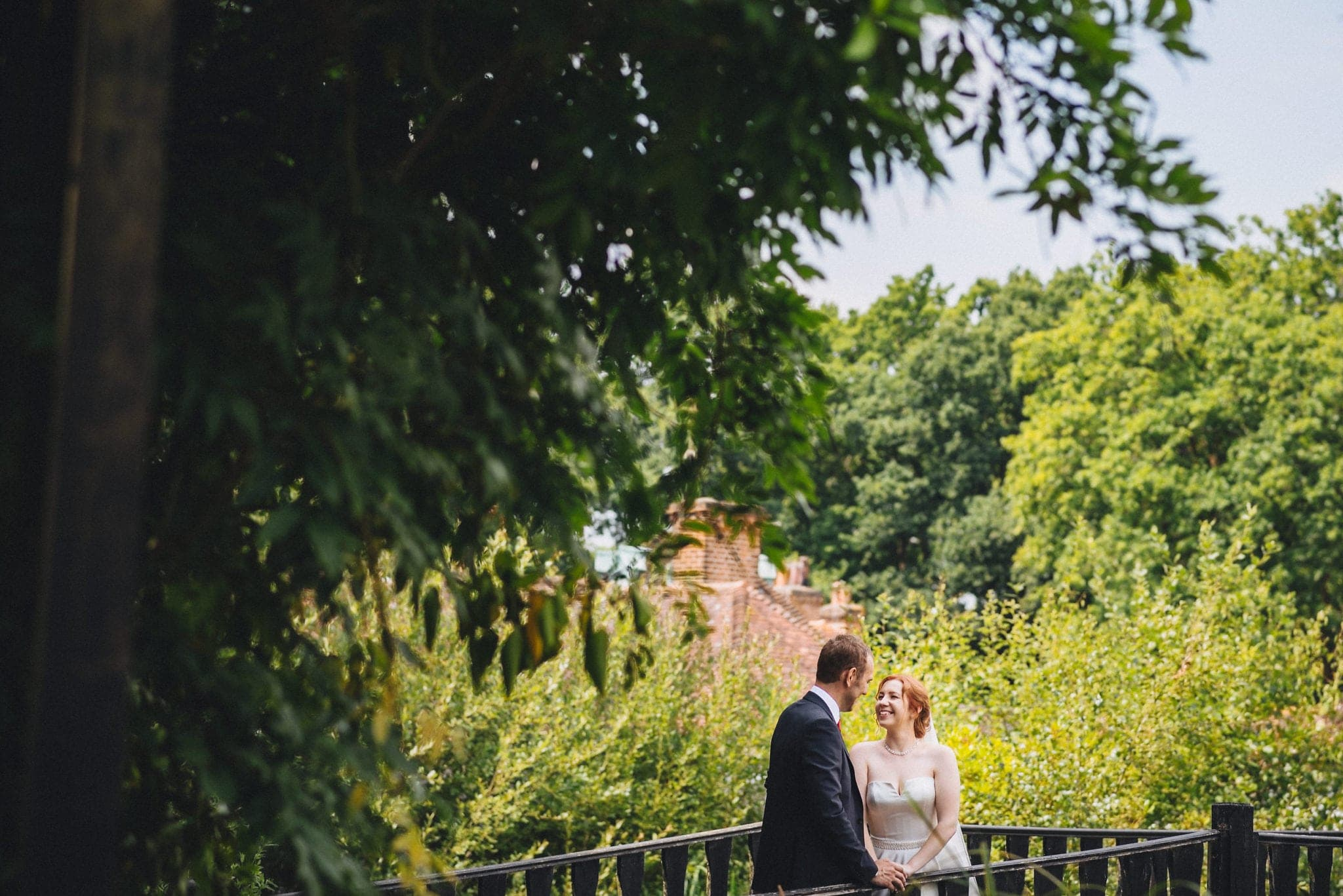 Bride and groom laughing on bridge at Hever Hotel