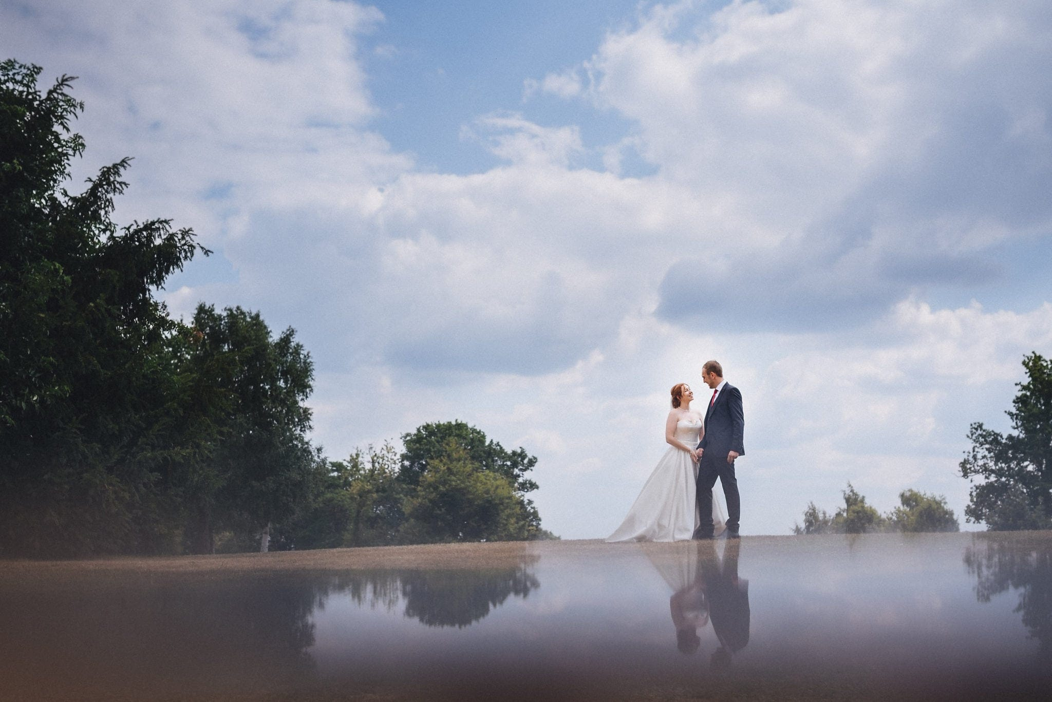 Bride and groom hold hands at their joyful intimate Hever Hotel Wedding