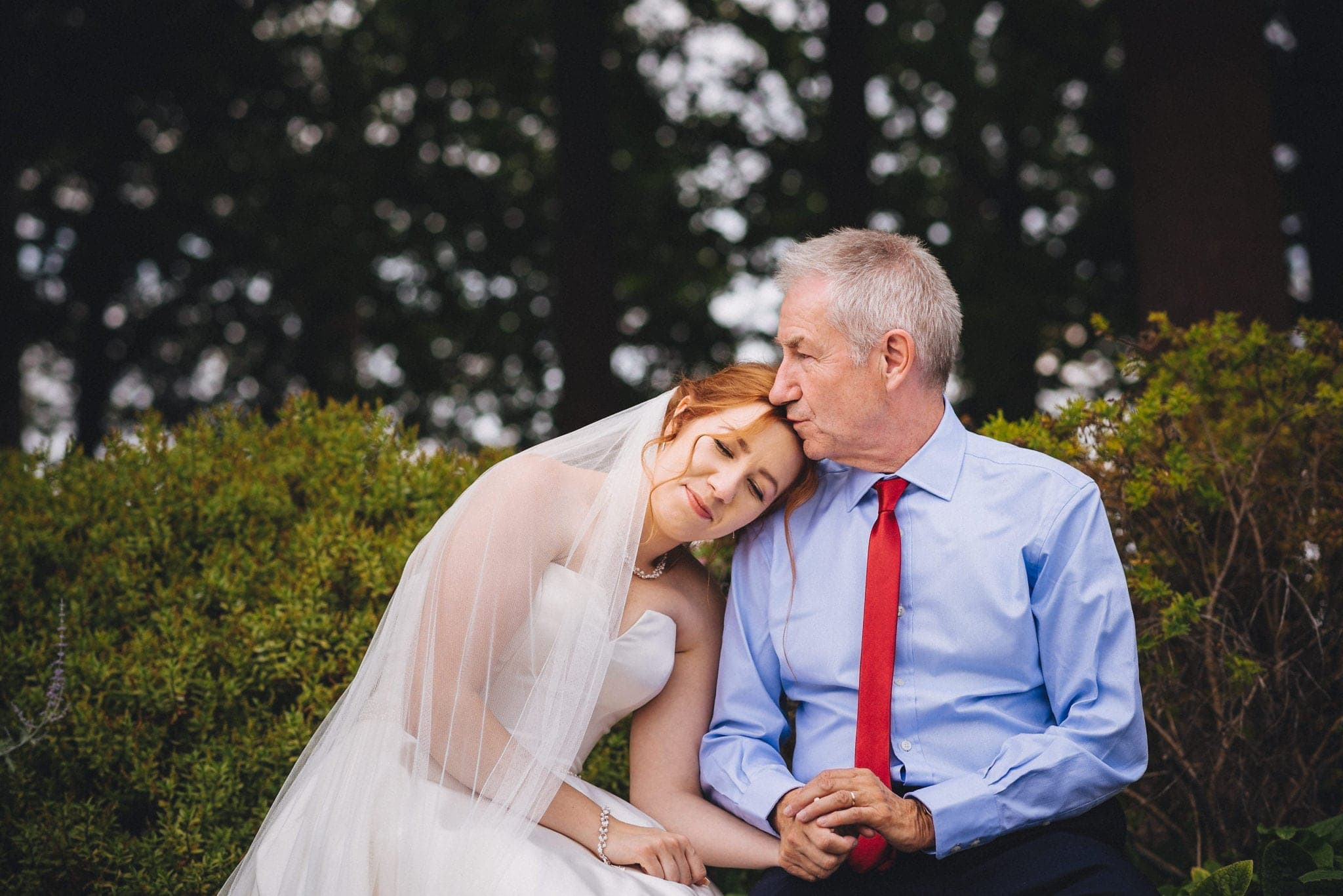 Bride leans her head on her father's shoulder