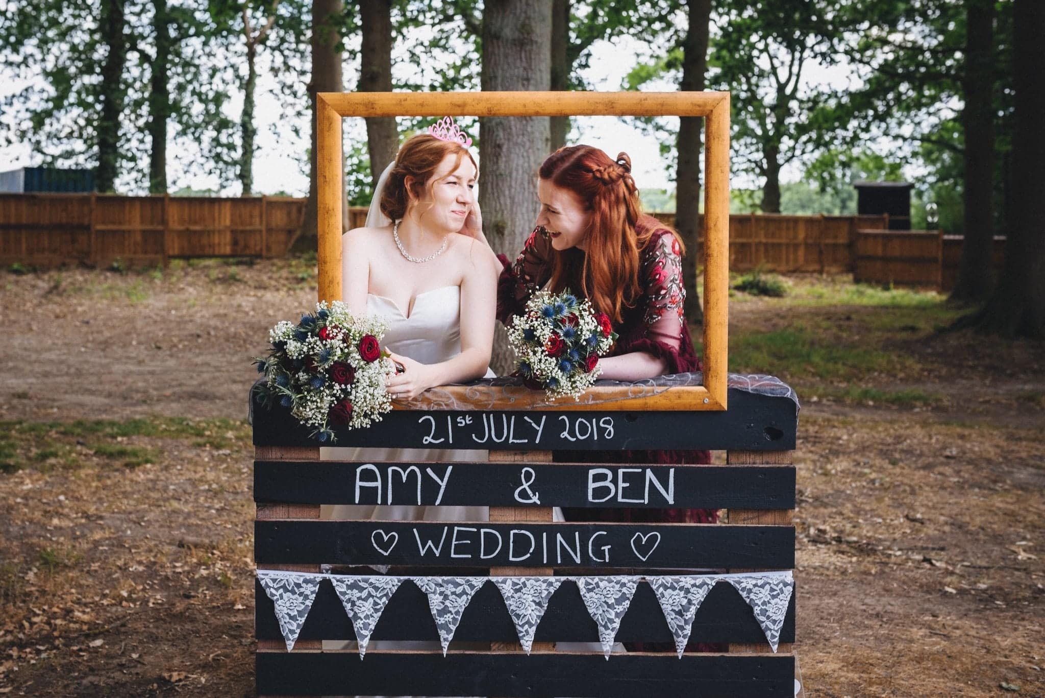 Bride poses with her sister in rustic photobooth in the grounds of Hever Hotel