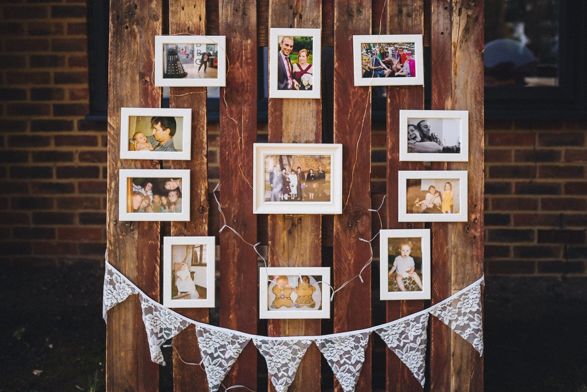 Framed photos of the bridal couple on a palette with fairylights and lace bunting
