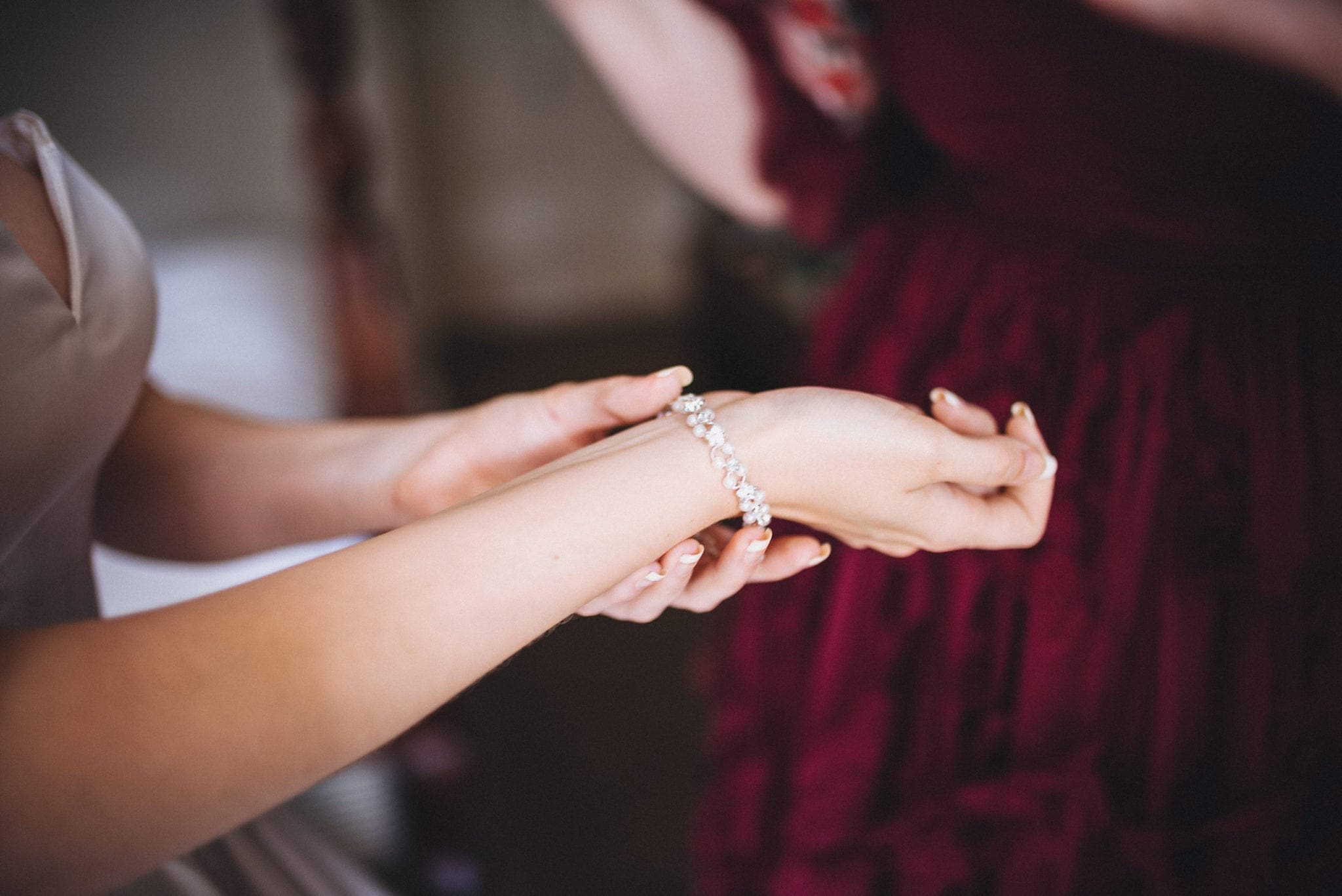 Bride fastens pearl bracelet as she gets ready for her intimate Hever Hotel wedding