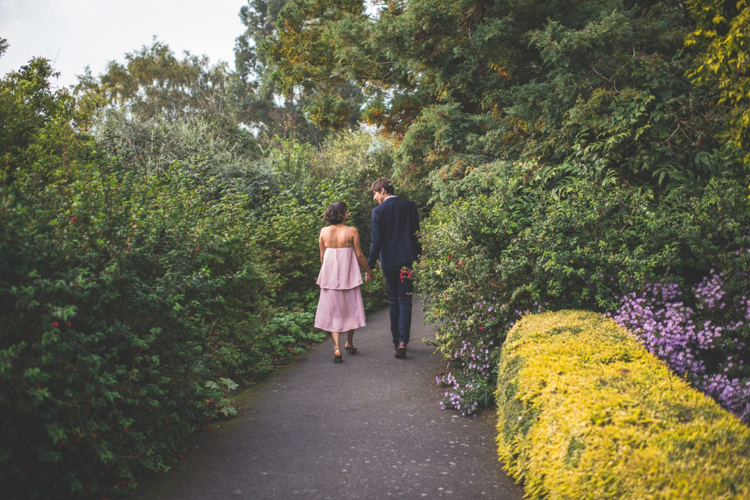 engaged couple walk down a colourful alley at a Hampstead pergola wedding