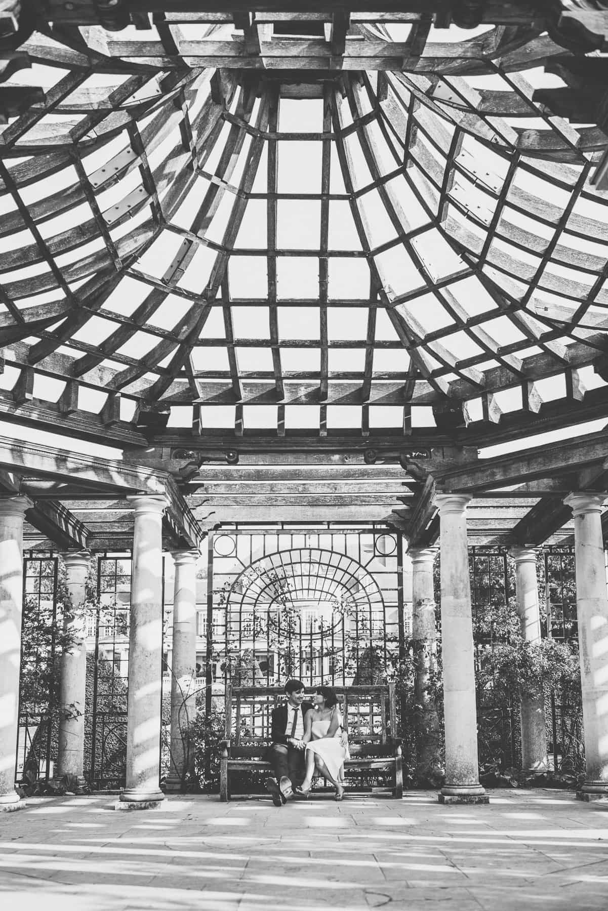 The stunning beam roof of the Hampstead Pergola surrounds the bride and groom cuddling on a bench