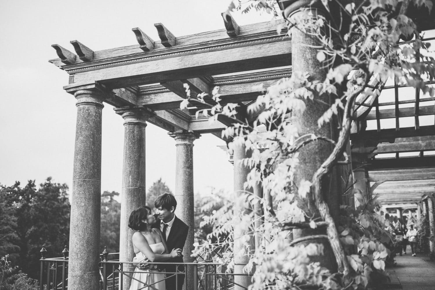 bride and groom lean against the banister at the pergola wedding venue