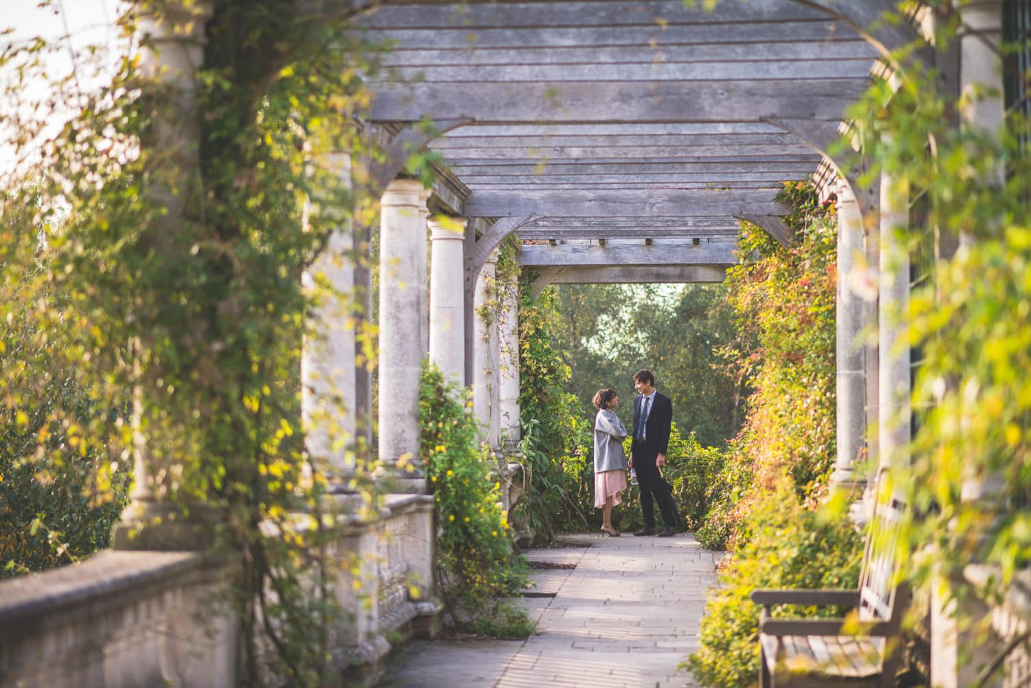 A couple standing surrounded by the luxurious columns of London's Hampstead Pergola