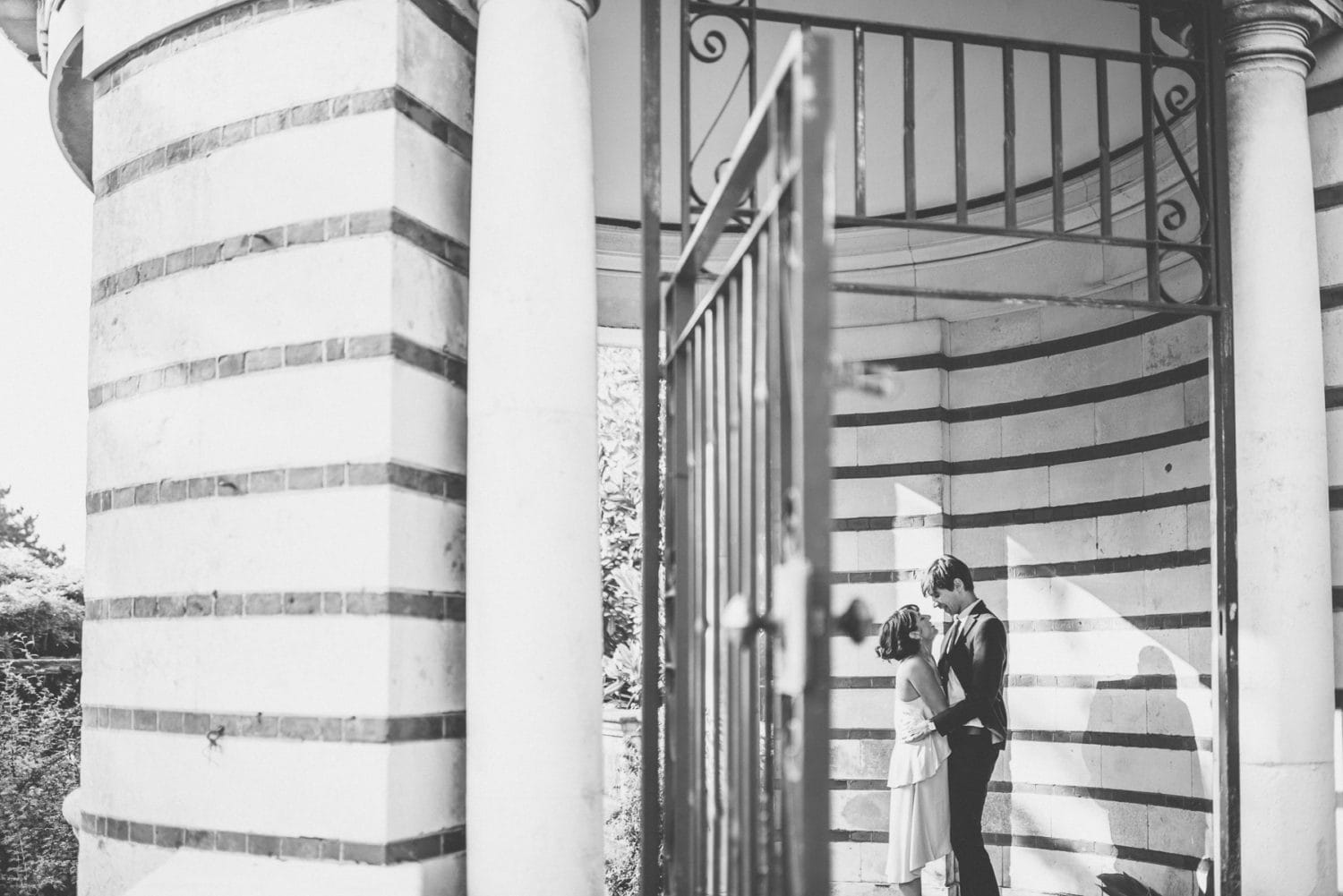 Couple hold hands in the stripy walls at the Hampstead Pergola and Hill Gardens